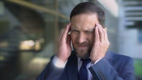 Mann leidet unter den Kopfschmerzen und oben massiert Tempel, schwindliger Effekt der Migräne, Abschluss stock video footage