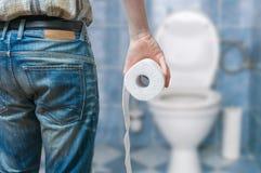 Mann leidet unter Diarrhöe hält Toilettenpapierrolle vor Toilettenschüssel Stockfotos