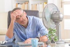 Mann leidet unter Hitze im Büro oder zu Hause Stockbild