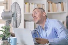 Mann leidet unter Hitze im B?ro oder zu Hause stockbild