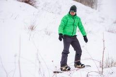 Mann lernt, auf einen Snowboard unten umzuziehen Stockbild