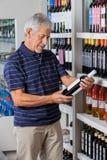 Mann-Leseanweisungen von der Alkohol-Flasche Stockfotos