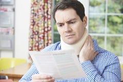 Mann-Lesebuchstabe, nachdem Nackenverletzung empfangen worden ist Stockbilder