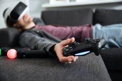 Mann liegt auf dem Sofa, welches die Gläser 3d trägt, die Steuerknüppel halten lizenzfreie stockfotos