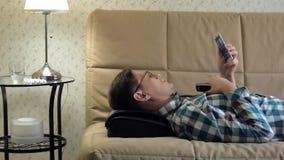 Mann liegt auf der Couch zu Hause, unter dem Kopf eines Massager, entspannter Zustand stock footage