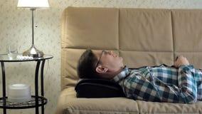 Mann liegt auf der Couch zu Hause, unter dem Kopf eines Massager, entspannter Zustand stock video