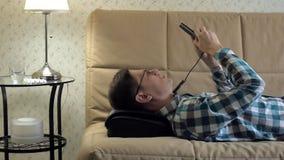 Mann liegt auf der Couch zu Hause, unter dem Kopf eines Massager, entspannter Zustand stock video footage