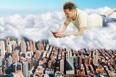 Mann liegt auf Wolken mit Smartphone über megapolis Stadtkonzept Lizenzfreies Stockfoto