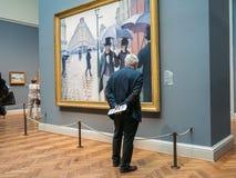 Mann liest Ausstellungsaufkleber für Caillebottes Paris-Straße, Kunst I Lizenzfreie Stockfotografie