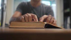 Mann liest ein Buch Ausbildungslernkonzeptbibliothek Mann öffnet das Buch Mannlebensstil dreht die Seiten des Buches stock video footage
