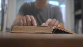 Mann liest ein Buch Ausbildungslernkonzeptbibliothek Mannlebensstil öffnet das Buch Mann dreht die Seiten des Buches stock footage