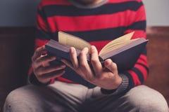 Mann liest ein großes Buch Stockbild