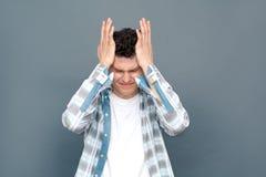 Mann lokalisiert auf dem grauen Wandfreistilstellungs-Holdingkopf, der migrain hat stockfotografie