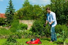 Mann mäht den Rasen am Sommer Lizenzfreies Stockbild