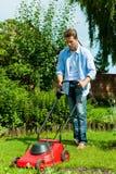 Mann mäht den Rasen am Sommer Lizenzfreies Stockfoto