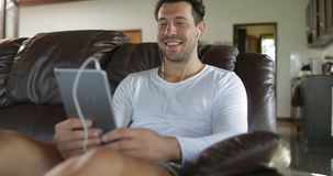 Mann machen on-line-Videoanruf unter Verwendung Tablet-Computer-Sit On Coach In Living-Raumes, lächelnder Guy Speaking Internet stock video