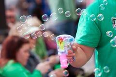 Mann macht Blasen mit Blasen-Pistole an der Parade Stockfoto