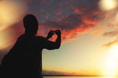 Mann macht ein Foto des Sonnenuntergangs auf Ihrem Smartphone Lizenzfreies Stockbild