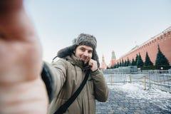 Mann macht ein Foto von gegen den Hintergrund eines roten Quadrats im Winter in Moskau, Russland Lizenzfreies Stockbild