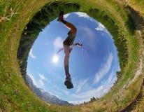 Mann macht einen Sprung in einer Bergwiese Ansicht von unterhalb Tageslicht Stockfotos