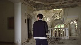 Mann macht Fotos des alten Innenraums durch Kamera in verlassenem Palast stock video footage