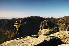 Mann macht Fotos durch Smartphone auf Spitze im Felsenreichpark und passt über nebelhaftes Tal des Herbstes auf Lizenzfreie Stockbilder