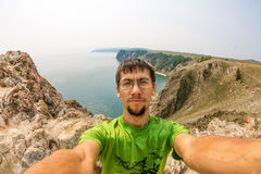 Mann macht selfie auf den Felsen durch das Meer Lizenzfreie Stockbilder