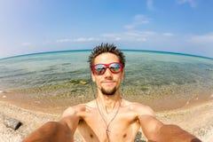 Mann macht selfie auf den Felsen durch das Meer Lizenzfreies Stockbild