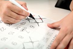 Mann markiert Tage auf dem Kalender mit Markierung lizenzfreie stockbilder