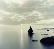 Mann meditiert auf dem See lizenzfreies stockbild