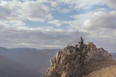 Mann meditiert auf einem Felsen an einem sonnigen Tag Stockfotos