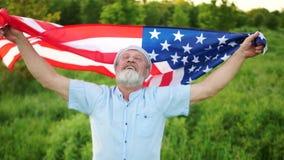 Mann mit amerikanischer Flagge im Park am sonnigen Tag US-Unabh?ngigkeitstag, patriotischer Tag stock video footage