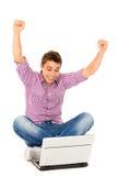 Mann mit Arme angehobenem Sitzen mit Laptop Stockbild