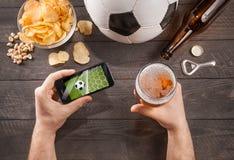 Mann mit aufpassendem Fußballspiel des Bieres auf smarphone Lizenzfreie Stockfotografie