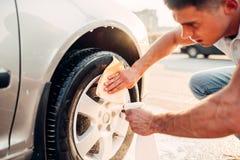 Mann mit Auto fasst Reiniger, Autowäschen ein Stockbilder