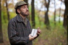 Mann mit Bart öffnet die Flasche im Herbstwald Stockfoto