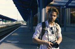 Mann mit Bart hält photocamera auf Stationshintergrund Städtisches Foto und reisendes Konzept Touristisch bereiten Sie vor, um zu Stockfotos