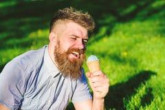 Mann mit Bart und dem Schnurrbart auf glücklichem Gesicht isst Eiscreme, Gras auf dem Hintergrund, defocused Mann mit langem Bart lizenzfreies stockfoto