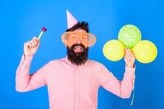 Mann mit Bart und dem Schnurrbart auf glücklichem Gesicht hält Luftballone, blauen Hintergrund Champagne mit den Fliegenballonen  Stockbilder