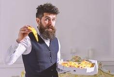 Mann mit Bart und dem Schnurrbart hält Kasten mit geschmackvoller frischer heißer Pizza Macho in der klassischen Kleidung hungrig stockfoto