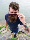 Mann mit Bart und dem Schnurrbart trägt Sonnenbrille, Wasseroberfläche auf Hintergrund Hippie auf dem Blinzeln des Gesichtes, das Lizenzfreie Stockfotografie