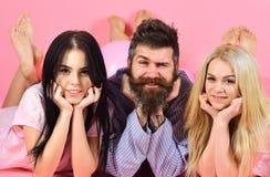 Mann mit Bart und dem Schnurrbart zieht die blonde und Brunettemädchen an Mädchen verlieben sich in bärtigen Macho-, rosa Hinterg Lizenzfreie Stockbilder