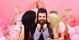 Mann mit Bart und dem Schnurrbart zieht die blonde und Brunettemädchen an Mädchen verlieben sich in Macho und küssen, rosa Hinter Lizenzfreie Stockfotografie
