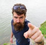 Mann mit Bart und Schnurrbart mit Sonnenbrille, Flussufer auf Hintergrund Hippie auf ernstem Gesicht zeigend mit dem Zeigefinger Lizenzfreie Stockfotografie