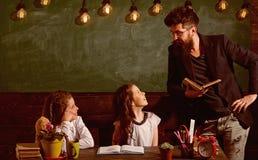 Mann mit Bart unterrichtet Schulmädchen, Lesebuch Neugierige nette Kinderhörender Lehrer mit Aufmerksamkeit lehrer lizenzfreies stockfoto