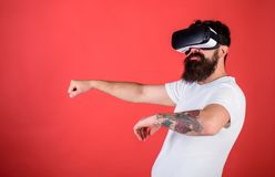 Mann mit Bart in VR-Gläsern, die Auto, roten Hintergrund fahren Virtuelles Konzept der treibenden Lektionen Hippie auf überzeugte Stockfotografie