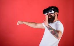 Mann mit Bart in VR-Gläsern, die Auto, roten Hintergrund fahren Virtuelles Konzept der treibenden Lektionen Hippie auf dem glückl Stockfoto