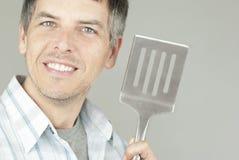 Mann mit BBQ-Flipper Stockfoto