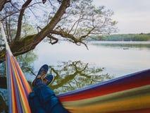Mann mit blauem Schuh- und Jeansschwingen in der bunten H?ngematte h?ngt am Ufer des Sees in D?nemark lizenzfreies stockbild