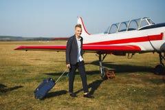 Mann mit blauer Reisetasche nahe einem Flugzeug Reise auf privaten kleinen Flugzeugen lizenzfreies stockfoto